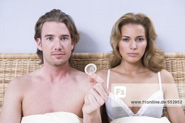 Porträt jungen Paares sitzen im Bett Mann  hält Kondom