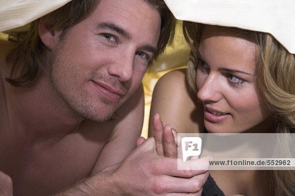 Porträt jungen Paares hält hände unter Bettdecke
