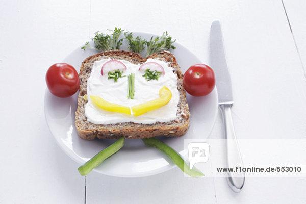 Sandwich mit Frischkäse und Gesicht aus verschiedenen Gemüse gebildet