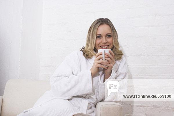 Porträt von lächelnd junge Frau im Bademantel auf halten Mug Sessel sitzend
