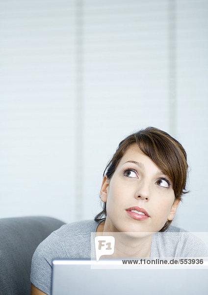 Junge Frau auf der Couch  mit Laptop