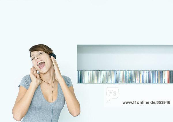 Junge Frau hört Kopfhörer und singt  neben CD-Reihe  Augen geschlossen
