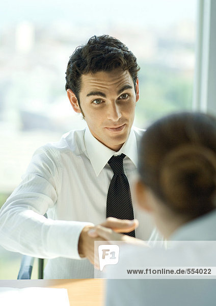 Young male professional shaking hands across table