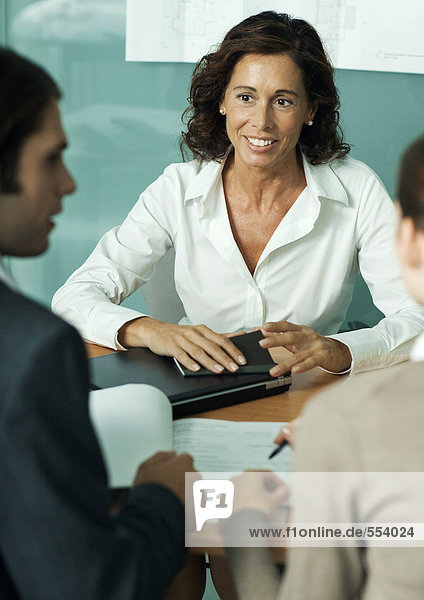 Mature female professional sitting across from clients  smiling