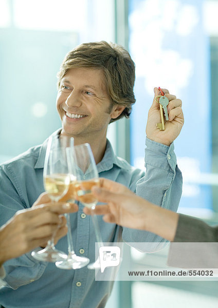 Toasting with glasses of champagne  focus on man holding up keys in background