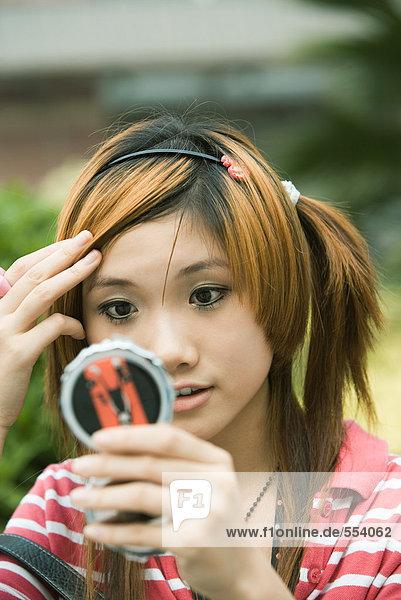 Junge Frau betrachtet sich selbst im Taschenspiegel