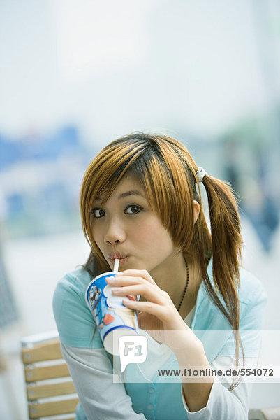 Junge Frau trinkt Fast Food Drink  schaut in die Kamera