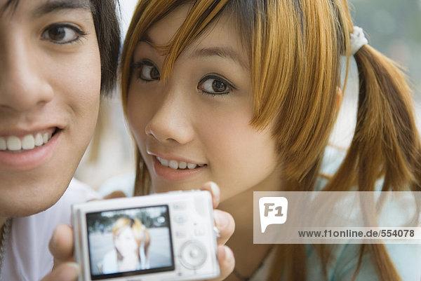 Junges Paar hält Digitalfoto mit Frauenfoto hoch