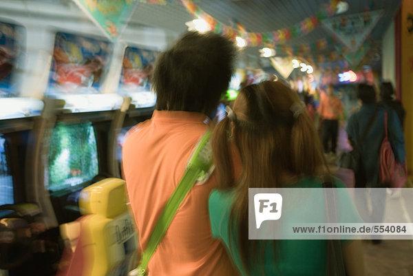 Junges Paar in der Videospielhalle  Rückansicht