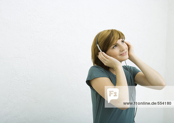 Junge Frau hört Kopfhörer  lächelt und schaut auf.
