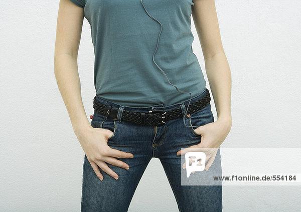Junge Frau stehend mit Daumen in Jeanstaschen  Nahaufnahme Mittelteil