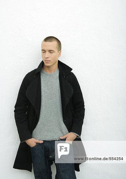 Junger Mann im Mantel  stehend mit Händen in Taschen und Augen geschlossen  Portrait