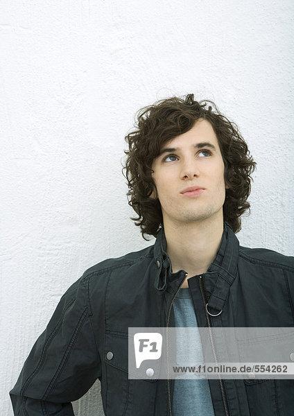 Junger Mann schaut nach oben  Portrait  weißer Hintergrund