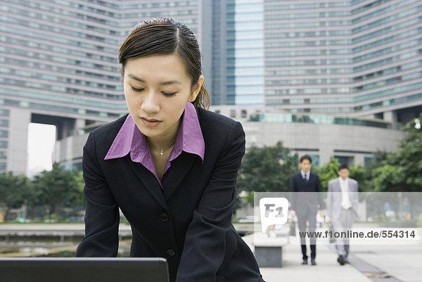 Geschäftsfrau beim Bücken im Büropark