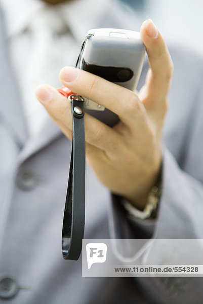 Businessman holding cell phone in hand  close-up