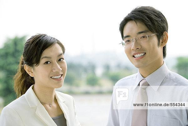 Zwei Geschäftsleute  lächelnd vor der Kamera  Kopf und Schultern  Portrait
