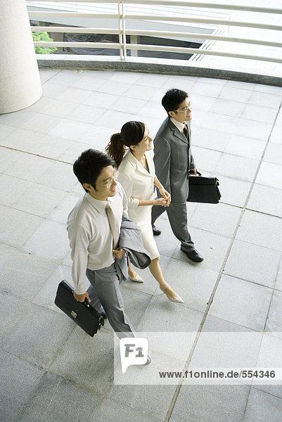 Drei Geschäftsleute gehen Seite an Seite  hoher Blickwinkel