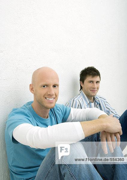 Zwei junge Männer sitzen auf dem Boden und schauen in die Kamera.