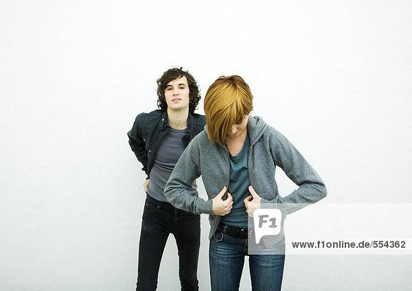 Zwei junge Erwachsene beim Anziehen von Jacken  weißer Hintergrund