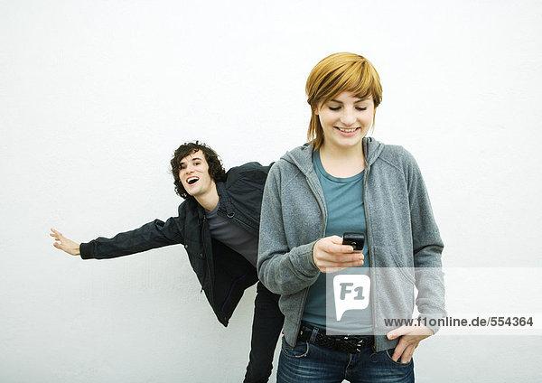 Junge Frau hält Handy während junger Mann hinter ihren Tänzen  weißer Hintergrund