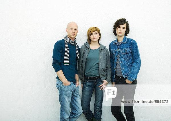 Drei junge Erwachsene  die sich an die Wand lehnen  auf die Kamera schauen  Portrait  weißer Hintergrund
