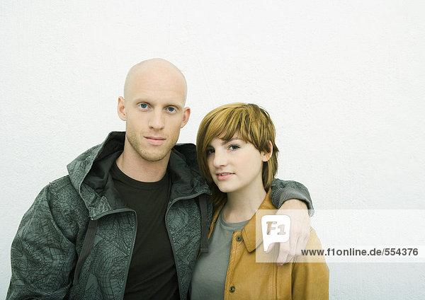 Junges erwachsenes Paar mit Blick auf die Kamera  Mann mit Arm um die Frau  Porträt