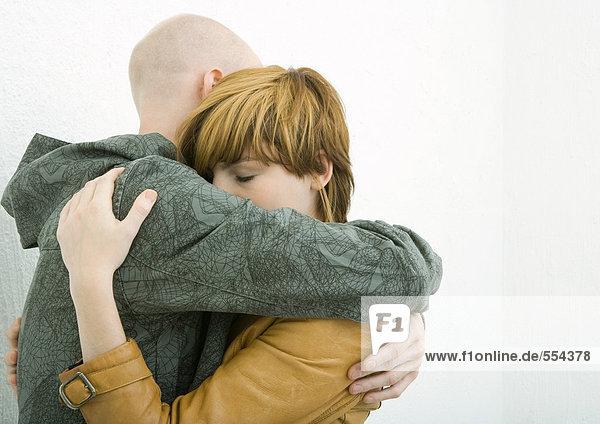 Junges erwachsenes Paar umarmt  Frau schließt Augen