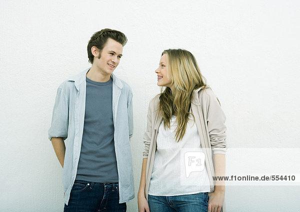 Junger Mann und junges Mädchen stehen Seite an Seite und lächeln sich an.