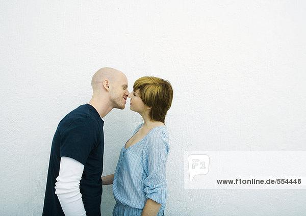 Junges Paar beim Küssen  Seitenansicht