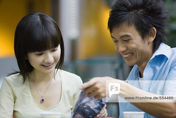 Junge Frau und junger Mann beim gemeinsamen Betrachten des Dokuments