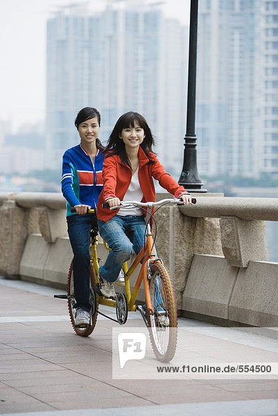 Two young women riding tandem bicycle