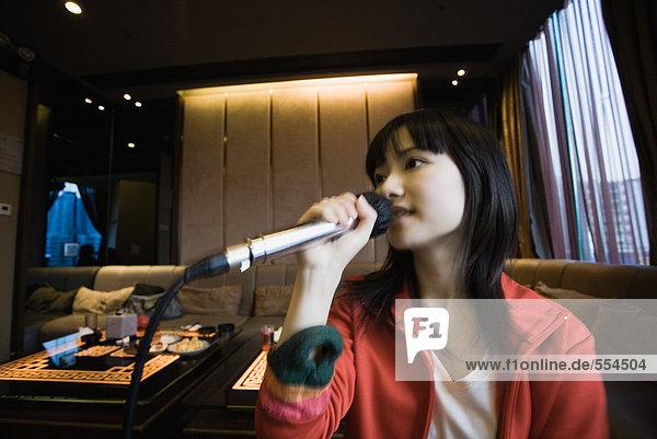 Junge Frau singt Karaoke