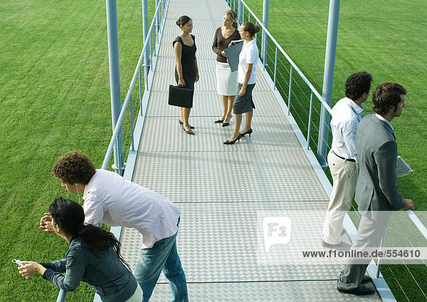 People standing in small groups on walkway  high angle view