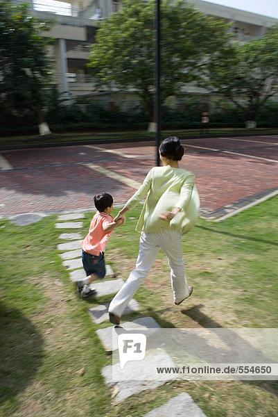 Mutter und Sohn gehen über das Gras in der Wohnanlage