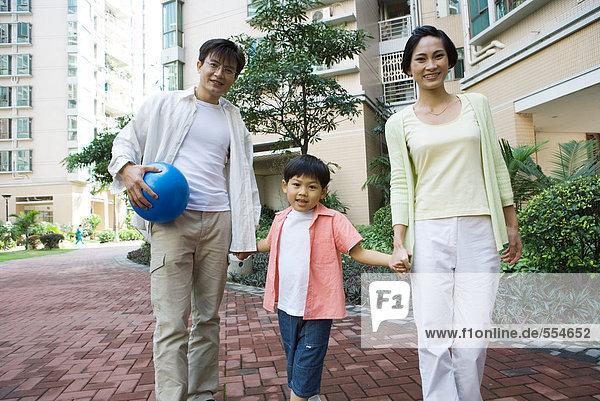 Familie steht am Appartementkomplex  lächelt in die Kamera  Vater hält Ball
