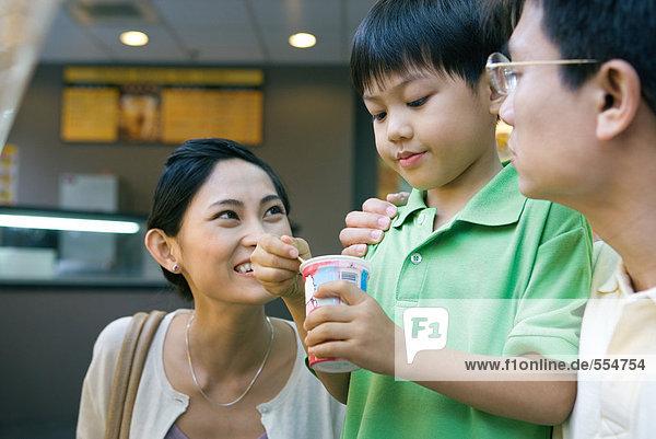 Junge isst süßen Snack  Eltern sehen zu.