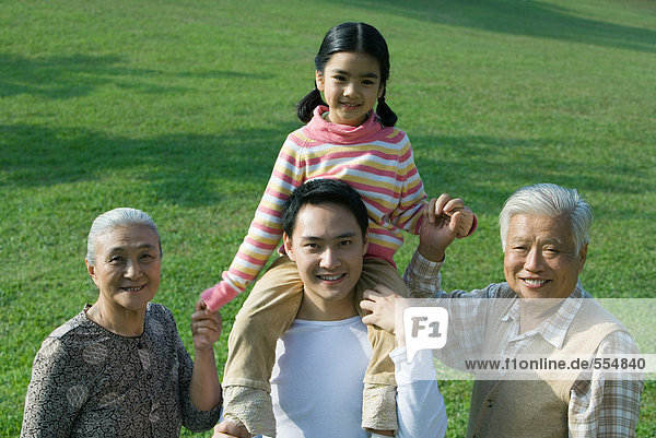 Three generation family  girl sitting on father's shoulders  holding grandparent's hands  portrait