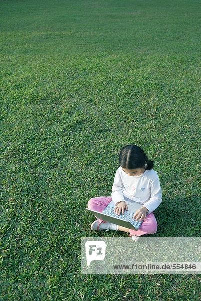 Mädchen im Gras sitzend mit Laptop