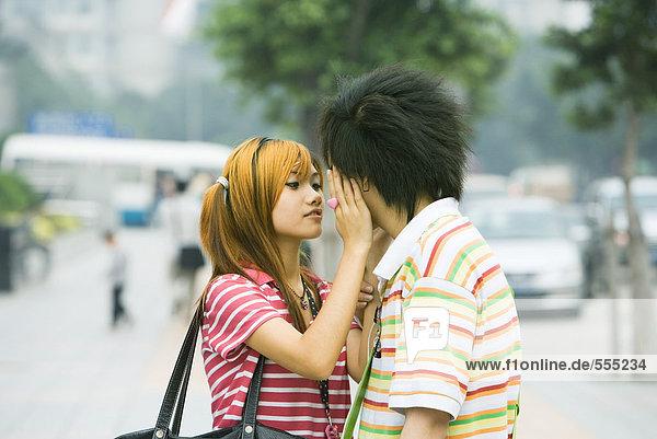 Teenager-Paar in urbaner Umgebung  Mädchen berührt Jungengesicht