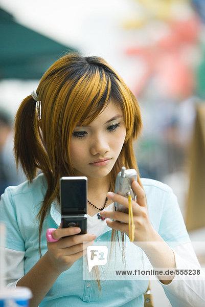 Teenager Mädchen mit zwei Handys