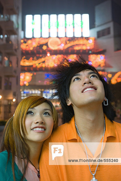 Teenager-Paar schaut nach oben  Lichter im Hintergrund