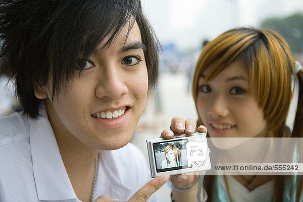 Teenager-Paar  Mann hält Digitalkamera mit Foto der Freundin in der Hand