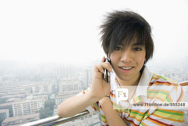Teenager Junge mit Handy  Stadtbild im Hintergrund