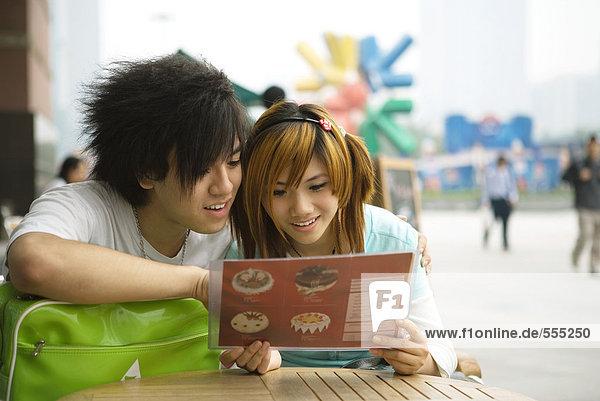 Teenager-Paar sitzt auf dem Bürgersteig Cafe  Blick auf die Speisekarte