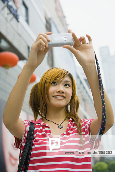 Teenagermädchen beim Fotografieren mit dem Handy
