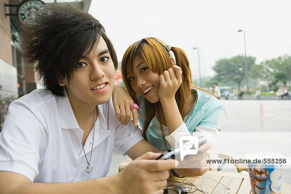 Teenager-Paar sitzend im Outdoor-Café  Junge mit Videospiel