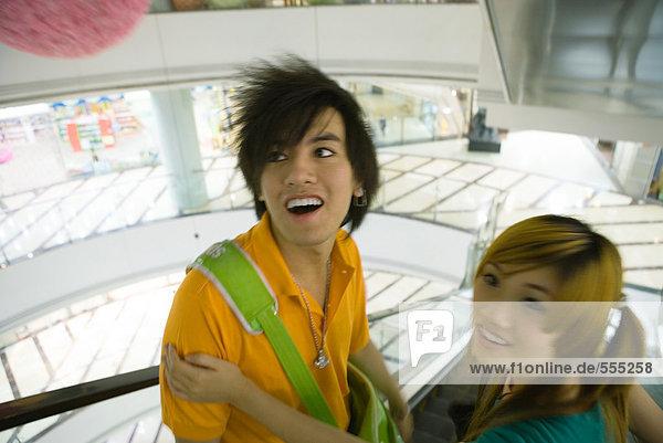 Teenager-Paar auf einer Rolltreppe im Einkaufszentrum  Blick in den hohen Winkel
