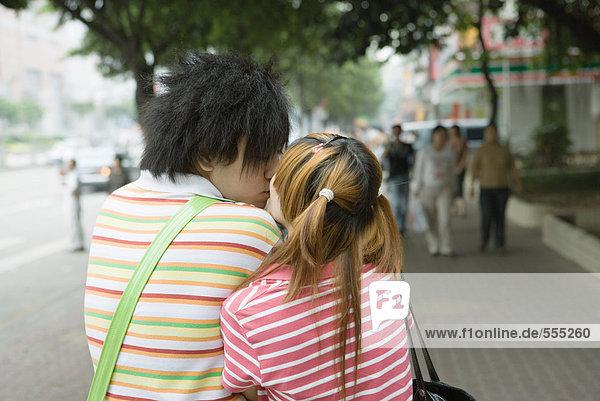 Teenagerpaar beim Küssen auf dem Bürgersteig  Rückansicht