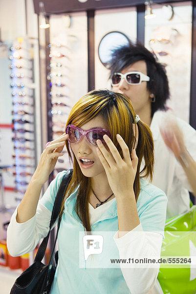 Teenager-Paar beim Anprobieren der Sonnenbrille im Laden
