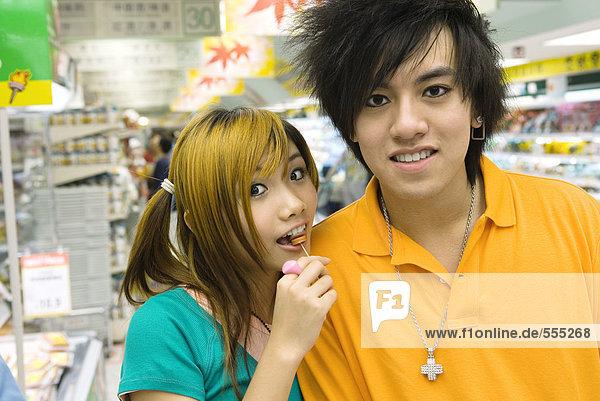 Teenager-Paar im Lebensmittelladen  Mädchen beim Lolliessen